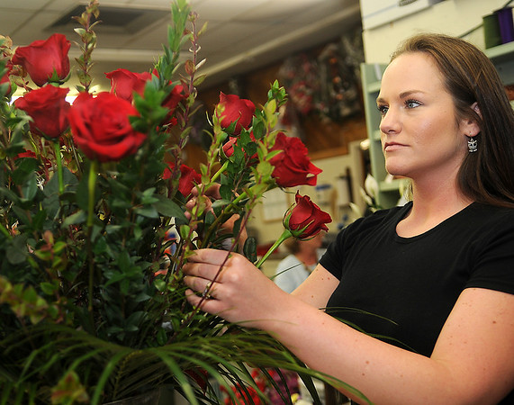 Chasie Bray completes a bouquet of red roses at Enid Floral and Gifts Thursday, Feb. 13, 2014. Several area florists have had to order additional roses to fill Valentine's Day orders. (Staff Photo by BONNIE VCULEK)