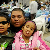Al Joseph (center) holds his children, Keja and Wayna, after they received free dental care during the 5th annual Oklahoma Mission of Mercy at the Chisholm Trail Expo Center Friday, Feb. 7, 2014. Joseph arrived at the Garfield County fairgrounds at 4 a.m. so his children would be among the first 750 patients to receive care. OkMOM continues through Saturday. (Staff Photo by BONNIE VCULEK)