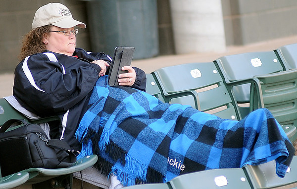 Jackie Johnson, an instructor at NOC Enid, relaxes with a good book between NOC Enid softball games at David Allen Memorial Ballpark Friday, Feb. 28, 2014. (Staff Photo by BONNIE VCULEK)