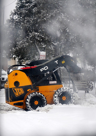 "Tires on a piece of heavy equipment spin as the driver gets stuck on the curb near a ""No Parking"" sign during snow removal at St. Mary's Regional Medical Center Tuesday, Feb. 04, 2014. (Staff Photo by BONNIE VCULEK)"