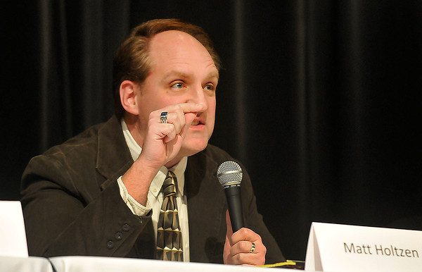 Enid High School teacher, Matt Holtzen, gestures as he makes his opening remarks as a panelist Tuesday during a community meeting on education at Waller Middle School. (Staff Photo by BILLY HEFTON)