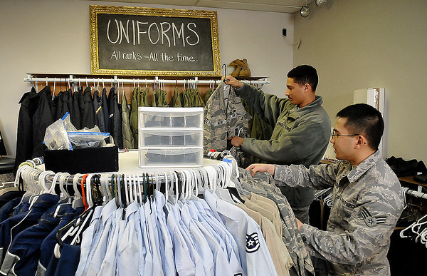 Senior Airman Mark Tumbagon and A1C Torrence Johnson look through uniforms at the Airman's Attic at Vance Air Force Base. (Staff Photo by BILLY HEFTON)