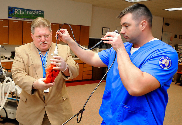 Respiratory Care program director, Dr. Deryl Gulliford, holds a pig lung as student, Mark Ousley, takes a look inside during an open house Sunday at Autry Technology Center. (Staff Photo by BILLY HEFTON)