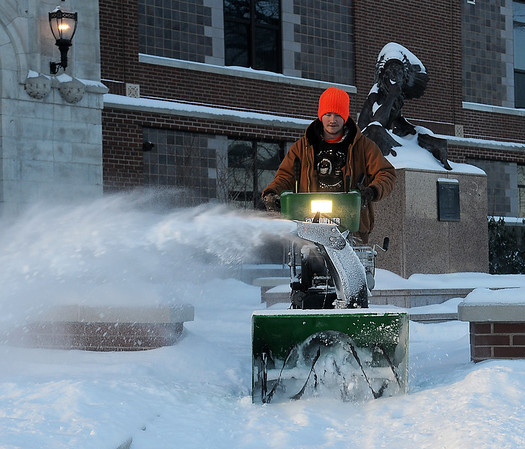 Logan Hubbart clears snow and ice from the entrance to Enid High School Tuesday, Feb. 11, 2014. Another winter storm with dangerous wind chills dumped additional snow forcing many schools across Enid and the state to close. (Staff Photo by BONNIE VCULEK)