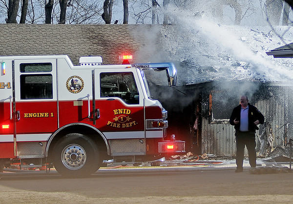 A stream of foam douses embers at a residential fire as Deputy Chief Ken Smith assists at the scene Saturday, Feb. 22, 2014. (Staff Photo by BONNIE VCULEK)