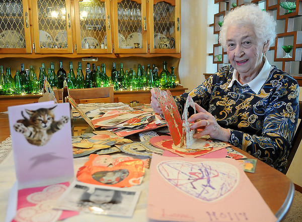 Helen Klein glances up as she looks at valentines received by five generations of her family in her home in Enid Thursday, Feb. 13, 2014. The valentines date from the 1890s through Thursday, Feb. 13, 2014. (Staff Photo by BONNIE VCULEK)