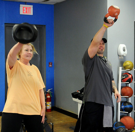 Linda Coffin follows the workout instruction of her Finer Physiques' personal trainer, Trevor Chambers, Wednesday, Feb. 12, 2014. (Staff Photo by BONNIE VCULEK)