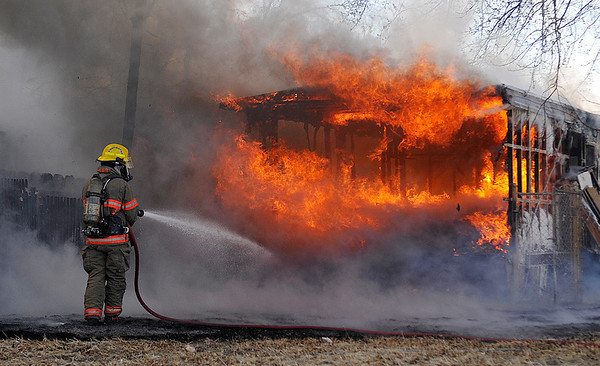 An Enid firefighter begins to fight a trailer fire in the 2700 block of north Adams Wednesday. (Staff Photo by BILLY HEFTON)