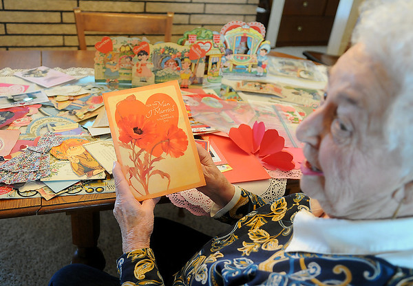 Helen Klein holds a valentine that she has been resending to her husband, Thom, for several years. Klein has a valentine collection that spans five generations of her family, dating back to the 1890s. (Staff Photo by BONNIE VCULEK)