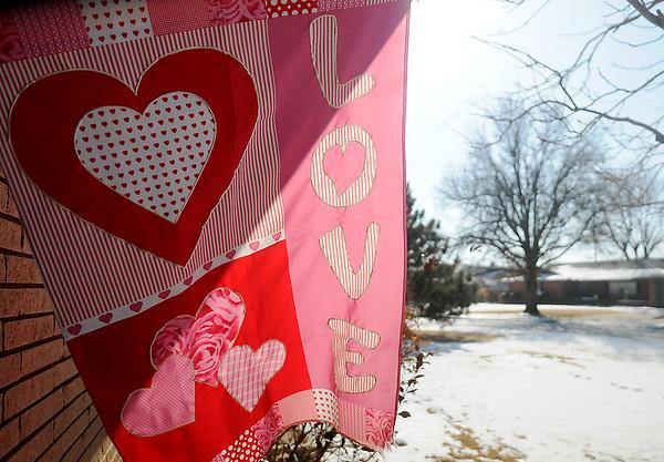 Sunlight illuminates a valentine's day flag Thursday, Feb. 13, 2014. (Staff Photo by BONNIE VCULEK)