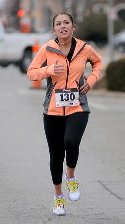 Laura Sheldon completes her run in 25:00, finishing as the overall female runner and first in the female 20-29 age group during the Junior Welfare League Warm Your Heart 5K in downtown Enid Saturday, Feb. 01, 2014. (Staff Photo by BONNIE VCULEK)