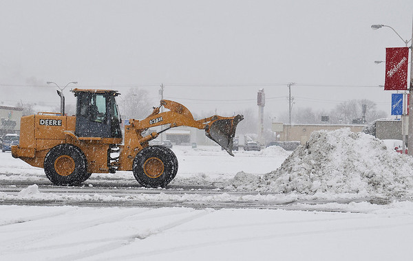 A front end loader clears snow from the Sunset Plaza parking lot as snow contines to fall Tuesday morning. (Staff Photo by BILLY HEFTON)