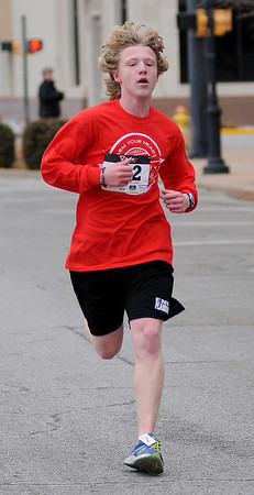 Gavin Lack, who attends Enid High School, sprints to a 20:12 time in the Junior Welfare League's Warm Your Heart 5K, finishing as the overall male winner Saturday, Feb. 01, 2014. (Staff Photo by BONNIE VCULEK)