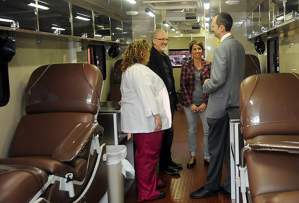 Melissa Bonniksen and Dr. Walter Kelley, from Oklahoma Blood Institute, visit with Dr. David Vanhooser and his wife, Stephany, during a tour of the new OBI Coach Friday, Feb. 28, 2014. (Staff Photo by BONNIE VCULEK)