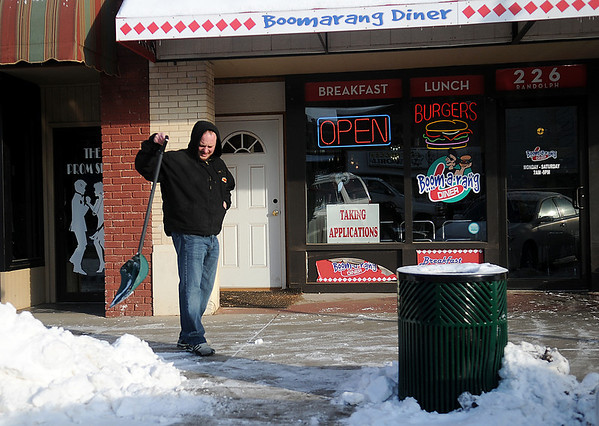 Matt Johnson, the manager at Boomarang Diner, clears snow and ice from the restaurant's sidewalk entrance at 226 W. Randolph Thursday, Feb. 6, 2014. (Staff Photo by BONNIE VCULEK)