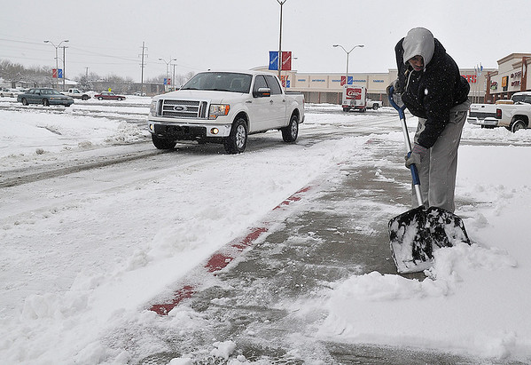 Alex Lofton shovels snow from the sidewalk at Sunset Plaza Tuesday. (Staff Photo by BILLY HEFTON)
