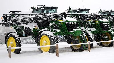 John Deere farming equipment is obscured by heavy snowfall in Enid Saturday, Feb. 28, 2015. (Staff Photo by BONNIE VCULEK)