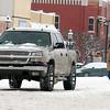 A pedestrian walks across N. Grand as snow continues to fall in downtown Enid Saturday, Feb. 28, 2015. (Staff Photo by BONNIE VCULEK)