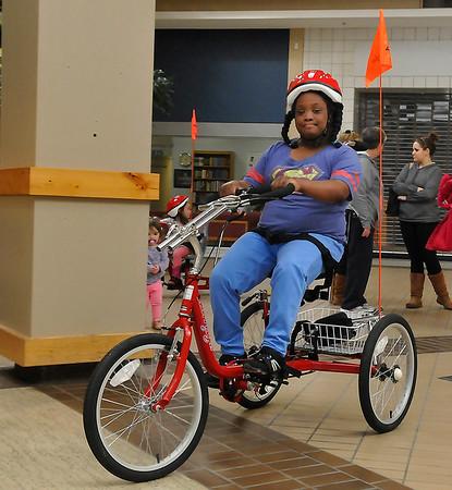 Destinee Sullivan rides her new AmTryke Thursday at Oakwood Mall. (Staff Photo by BILLY HEFTON)