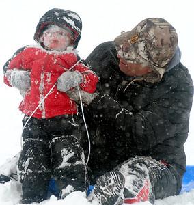 Gabriel Ward (left) and his grandpa, John Russell, survive a slide down the N. Van Buren overpass hill Saturday, Feb. 28, 2015. (Staff Photo by BONNIE VCULEK)