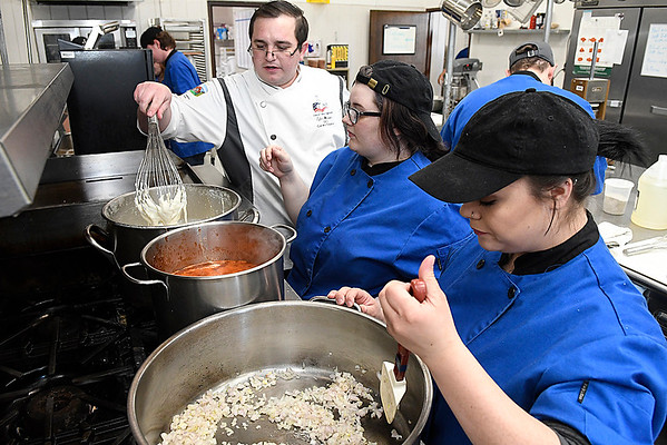 Chef Tyler Whitson works with students, Catherine Wolfe and Stephanie Mitchell, during culinary arts class at Autry Technology Center Wednesday February 15, 2017. (Billy Hefton / Enid News & Eagle)