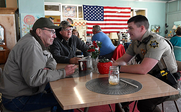 Garfield County deputy, Kyle Pierce, visits with Fred White and Wendell Vencl Saturday February 25, 2017 during a meet and greet at Teacups and Treasures in Garber. The town of Garber has contracted with sheriff's office for it's law enforcement. (Billy Hefton / Enid News & Eagle)