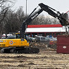 A tract hoe loads a container with debris of the trees being removed on the corner of Garriott and Garland to make way for a planned Jiffy Trip store. (Billy Hefton / Enid News & Eagle)