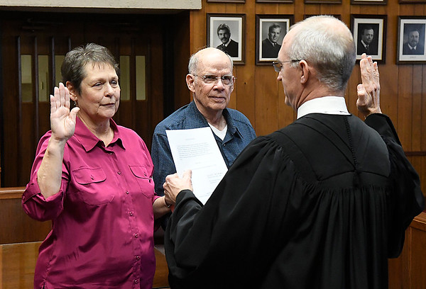 Clyde Sanford (center) hold a bible as Carolyn Sanford takes the oath of office for the Garfield County Assessor from District Judge Paul Woodward Monday February 5, 2018 at the Garfield County Courthouse. (Billy Hefton / Enid News & Eagle)