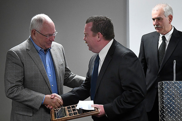 Enid police officer, Sgt. Eric Reddick, to congratulated by Dr. Richard DeVaughn and Police Chief Brian O'Rouke after being named Enid Police Officer of the Year during a ceremony Monday Febraury 5, 2018 at the Enid Fire Department. (Billy Hefton / Enid News & Eagle)
