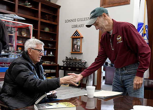 Bob Ford presents a copy of his book, Black Cat 2-1 and a coin to Bill Templin during an interview Wednesday February 7, 2018 at the M.L. Becker Educational Center at Woodring Vetetrans Park. (Billy Hefton / Enid News & Eagle)