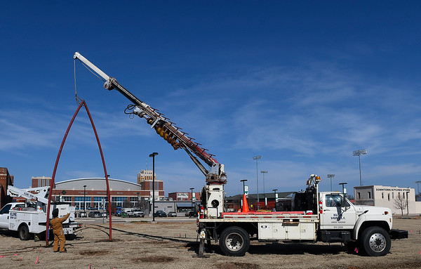 """Workers secure the first section of the art project """"Under Her Wing was the Universe"""" into place Monday February 4, 2019 in downtown Enid. (Billy Hefton / Enid News & Eagle)"""