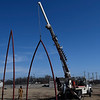 """A crane lifts a section of the art project """"Under Her Wing was the Universe"""" Monday February 4, 2019 in downtown Enid. (Billy Hefton / Enid News & Eagle)"""
