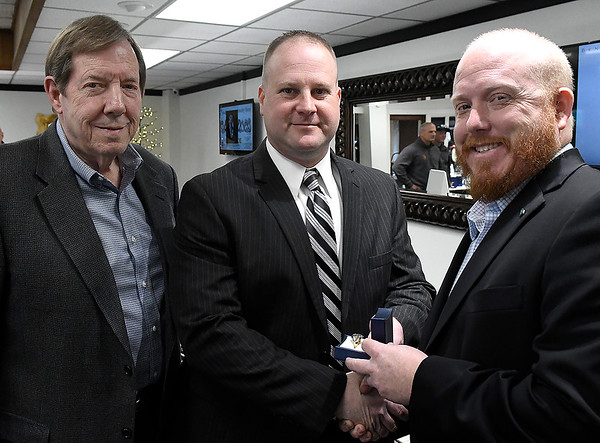 Curt Jackson (left) and Ryan Jackson (right), from Jackson Diamond Jewelers, present Nick John with a ring for being named Enid police officer of the year. (Billy Hefton / Enid News & Eagle)