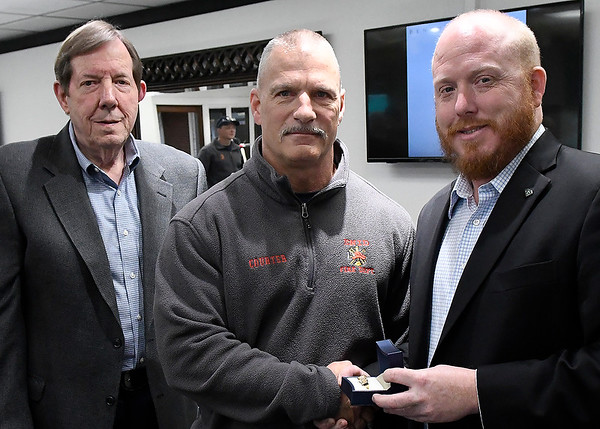 Curt Jackson (left) and Ryan Jackson (right), from Jackson Diamond Jewelers, present Mavick Courter with a ring for being named Enid firefighter of the year. (Billy Hefton / Enid News & Eagle)