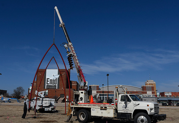 "A crane lifts a section of the art project ""Under Her Wing was the Universe"" Monday February 4, 2019 in downtown Enid. (Billy Hefton / Enid News & Eagle)"