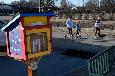 Samana Smith, Olivia Smith and Sophia Faulk walk their dogs pass the Little Free Library at the Cleveland Street Trailhead Thursday, February 4, 2021. (Billy Hefton / Enid News & Eagle)