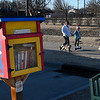 Samana Smith, Olivia Smith and Sophia Faulk walk their dogs pass the Little Free Library at the Cleveland Street Trailhead Thursday, February 4, 2021. (Billy Hefton / Enid News & Eagle)