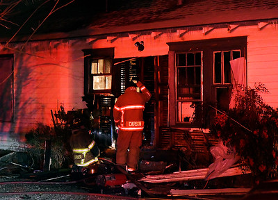Enid firefighters inspect the damage caused by a house fire  at 510 N. 8th Thursday, February 11, 2021. (Billy Hefton / Enid News & Eagle)