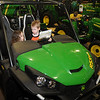 Megan and Spencer McGann check out the options in a John Deere Gator RSX850i during the 17th annual KNID Agrifest Saturday. (Staff Photo by BONNIE VCULEK)