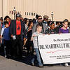 Members of the Dr. Martin Luther King, Jr. Holiday Commission and guests march around the downtown Enid square Sunday during the 25th annual holiday celebration Sunday. (Staff Photo by BONNIE VCULEK)