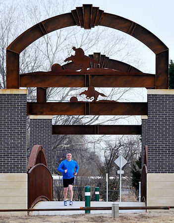 A man jogs across the Enid Trails bridge Sunday January 27, 2013 as temperatures approached 70 degrees. The National Weather Service is forecasting high temperatures near 80 degrees for Monday. (Staff Photo by BILLY HEFTON)