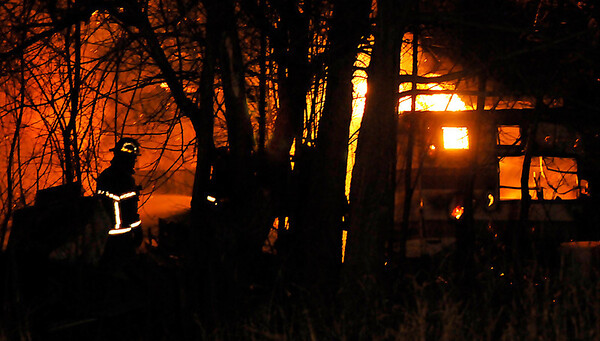 An Enid firefighter approaches a structure fire on east Popular Tuesday. (Staff Photo by BILLY HEFTON)