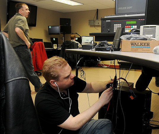 Lt. Ryan Singleton (top, left) oversees the work update on the 911 Communications Center at the Enid Police Department Tuesday as Richard Jordan, from Microdata in Denver, Col., connects the new phone lines. (Staff Photo by BONNIE VCULEK)