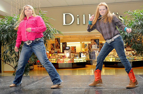 Madison and Brianna Deeds (from left) line dance during the Garfield County 4-H Day at Oakwood Mall Saturday. (Staff Photo by BONNIE VCULEK)