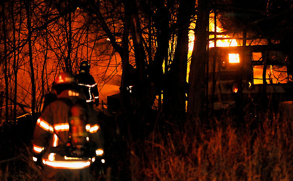 An Enid firefighters approaches a structure fire on east Popular Tuesday. (Staff Photo by BILLY HEFTON)
