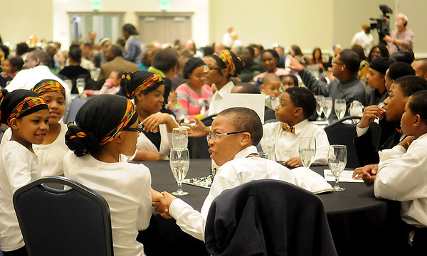 Guests greet each other as Chuck Kearney, the Dr. Martin Luther King, Jr. Commission Chairman, gives his opening remarks during the introduction of speakers Sunday at the 25th annual holiday celebration at Convention Hall. (Staff Photo by BONNIE VCULEK)