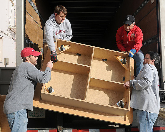 Junior Welfare League members' spouses and friends (from left) Doug Ratzlaff, Jonathan Bartley, Wayne McMillin and David Donaldson unload heavy platforms from an Atwood's semi-truck Saturday as the Junior Welfare League moves Return Engagement to its new location on Grand Avenue Saturday, Jan. 26, 2013. (Staff Photo by BONNIE VCULEK)
