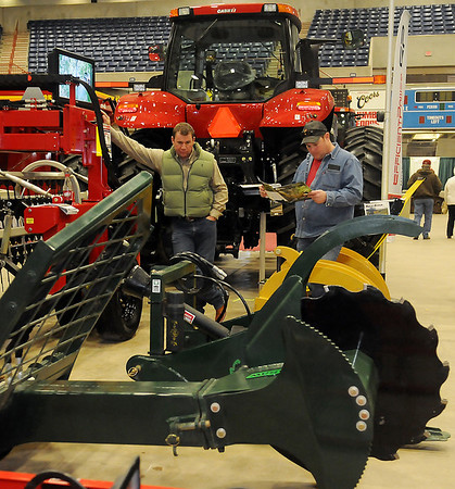 Arden Koehn, from Price Bros. Equipment Company in Wichita, Kan., visits with Casey Carr about a new TurboSaw Friday during the KNID Agrifest 2013 at the Chisholm Trail Expo Center Coliseum. (Staff Photo by BONNIE VCULEK)
