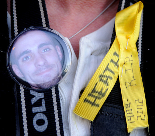 Teresa Sadler wears a photo button of Heath Crites and a yellow ribbon Tuesday, Jan. 22, 2013, during a candlelight vigil at Meadowlake Park North. Crites was killed in his home on Dec. 22, 2012, and the Enid Police Department continues their investigation into the unsolved murder. (Staff Photo by BONNIE VCULEK)