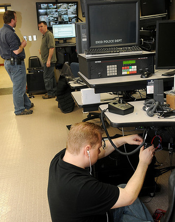 Jason Beckner, from Total Com, visits with Lt. Ryan Singleton (top, from left) as Richard Jordan, from Microdata in Denver, Col., connects the new phone lines during the 911 Communication Center update at Enid Police Department Tuesday. (Staff Photo by BONNIE VCULEK)